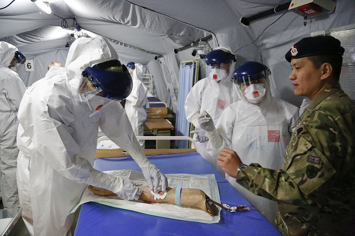 By DFID - UK Department for International Development - Practising taking blood in Ebola saftey suits, CC BY 2.0, https://commons.wikimedia.org/w/index.php?curid=38900972