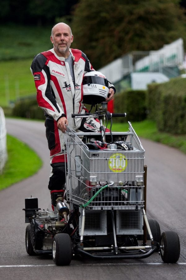 Matt Mckeown 55 stand's next to his hill climb vehicle a converted shopping trolley. Shelsley Walsh Hill Climb, Shelsley Walsh, Worcestershire. September 04, 2016. This is the bizarre moment a petrol head competed in a motorcycle road race - in a jet-powered SHOPPING TROLLEY. See NTI story NTITROLLEY. Madcap Matt McKeown, 55, of Plymouth, Devon, build his wacky racer - which has a top speed of 80mph - from an abandoned cart he found in a ditch. He bolted on brakes, go-kart wheels and a 150 horsepower engine from a Chinook helicopter before taking it for time trials. Matt first set a record of 45.5mph then made several tweaks and broke his own record by reaching 71.4mph at Elvington Airfield in North Yorks. On Sunday (4/9) Matt wowed the crowds when he competed in the Shelsley Walsh Hill climb in Worcestershire. Despite crawling up the 1,000 yard course - which hits a steep 1:7 incline at its peak - Matt wasn't last to finish and managed to beat a number of other conventional bikes.