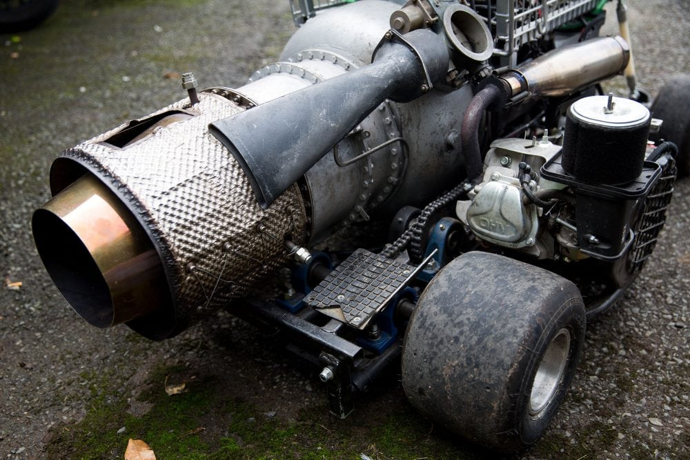 The jet engine of the converted shopping trolley. Shelsley Walsh Hill Climb, Shelsley Walsh, Worcestershire. September 04, 2016. This is the bizarre moment a petrol head competed in a motorcycle road race - in a jet-powered SHOPPING TROLLEY. See NTI story NTITROLLEY. Madcap Matt McKeown, 55, of Plymouth, Devon, build his wacky racer - which has a top speed of 80mph - from an abandoned cart he found in a ditch. He bolted on brakes, go-kart wheels and a 150 horsepower engine from a Chinook helicopter before taking it for time trials. Matt first set a record of 45.5mph then made several tweaks and broke his own record by reaching 71.4mph at Elvington Airfield in North Yorks. On Sunday (4/9) Matt wowed the crowds when he competed in the Shelsley Walsh Hill climb in Worcestershire. Despite crawling up the 1,000 yard course - which hits a steep 1:7 incline at its peak - Matt wasn't last to finish and managed to beat a number of other conventional bikes.