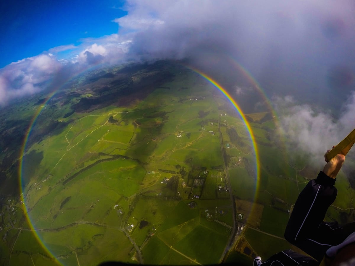 "Anthony Killeen gets the thrill of his life as he skydives over a 360 degree rainbow. See SWNS story SWRAINBOW; The British expat was on his first skydive with an instructor over New Zealand's Bay of Islands when he spotted the perfect circles of colour. Killeen said the rainbow kept its form until it was time to descend and land. ""All the instructors said they hadn't seen that before either - some had seen it from the plane, but never whilst diving."""