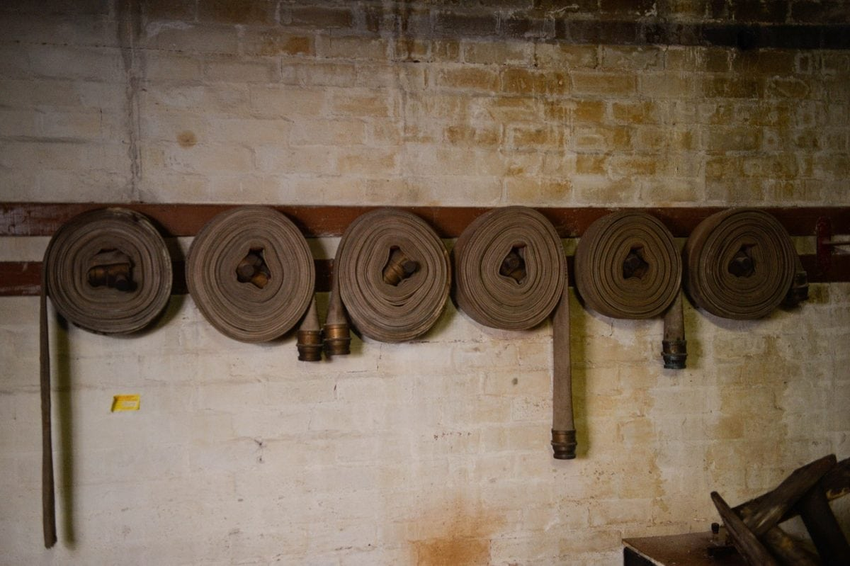 "Fabric hoses left coiled on the walls ready to be used. These remarkable pictures show a fire station which was left untouched for more than 60 years before it was discovered in the cellar of an old Co Op factory. See NTI story NTIFIRE. The secret fire station is complete with 1920s firefighting equipment, pumps, uniforms and coiled hoses. A half-drunk bottle of lemonade and exercise programmes were also found in the cellar of the former Co Op factory in Dudley, West Mids. Staff at shopfitting company The Allan Nuttall Partnership, which is now based in the building, heard rumours of a hidden fire station but dismissed it as an ""urban myth"". But when marketing manager Anna Bramford dug out some keys she was astonished to find fire regalia and pumps dating back to the 1920s."