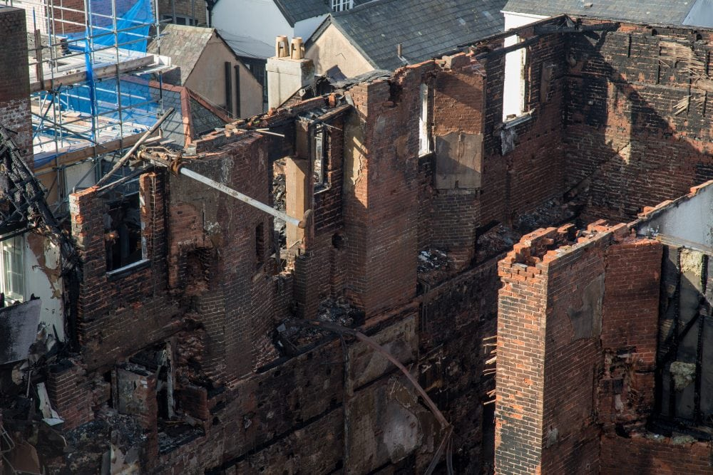"The damage to the Royal Clarence Hotel in Exeter can be seen from a fire fighters lift. 31 October 2016.  See SWNS story SWFIRE: A fire that wrecked England's oldest hotel has completely destroyed the 18th century building. The front of the hotel collapsed in the early hours and an extra eight fire engines rushed to the scene of the the front of the historic Royal Clarence Hotel in Exeter, Devon. People were advised by the emergency services to stay well away from the city centre as it was believed the hotel could completely collapse. An Exeter City Council chief, Karime Hassan, said: ""Key message this morning - please keep away from Cathedral Yard area and let emergency services do their job."""