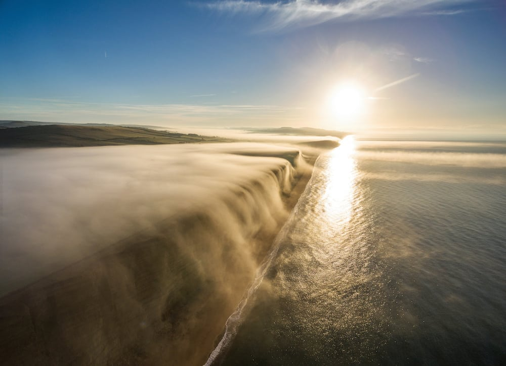 Mist is seen flowing off the cliff at West Bay, Dorset as the sun rises over the English channel, October 27 2016. The stunning footage was captured from a drone flying over the Jurassic Coast which is a World Heritage Site on the English Channel coast of southern England. It stretches from Exmouth in East Devon to Studland Bay in Dorset, a distance of about 96 mi,cliffs